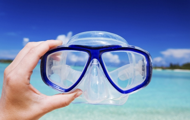 Hand holding snorkel googles against beach and sky
